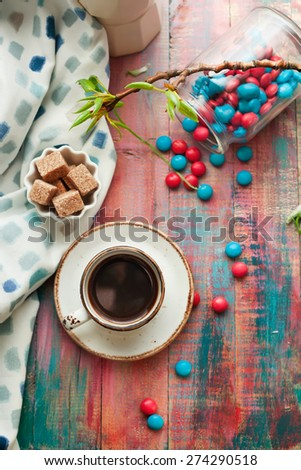 Cup of espresso with red and blue sweets on brightly colored wooden table, set with cane sugar and tree branch with fresh spring leaves - stock photo