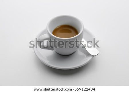 cup of espresso with saucer and spoon on white background
