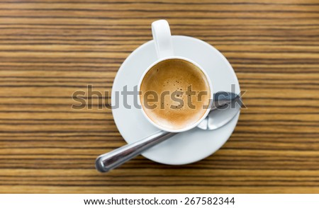 cup of espresso with teaspoon on strip wooden table top view. - stock photo