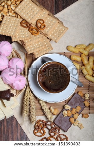 Cup of fragrant hot natural black coffee submitted with crackling cookies fresh sweet wafers and a cracker and pretzels