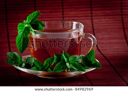Cup of fragrant tea with fresh leaves of green tea
