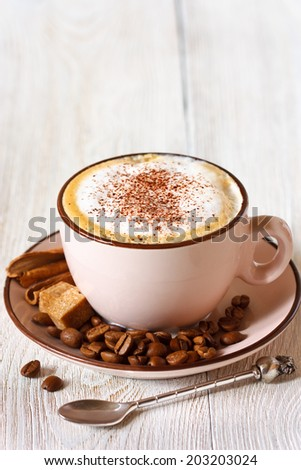 Cup of fresh cappucino coffee with coffee beans, brown sugar and cinnamon sticks close-up. - stock photo