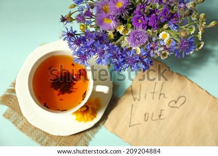 Cup of fresh herbal tea on table - stock photo