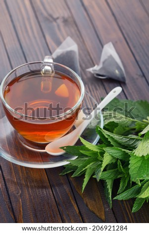Cup of fresh herbal tea  on wooden background. Selective focus, vertical.