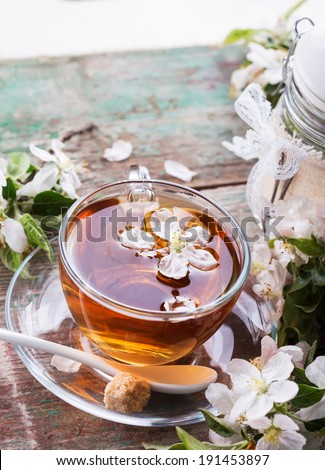 Cup of fresh herbal tea with spring flowers on vintage wooden table. Selective focus, vertical.