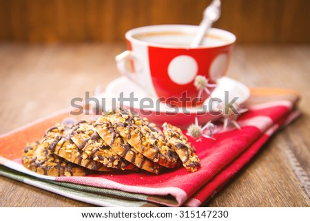 cup of fresh tea, with a c�ookies, on red textile - stock photo