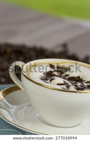 Cup of freshly brewed aromatic cappuccino coffee topped with milky froth and grated chocolate flakes served on a pretty napkin on a rustic wooden table - stock photo