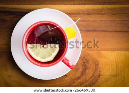Cup of freshly brewed healthy herbal tea with a lemon slice served in a red cup and white saucer on a wooden table with copy space, view from above - stock photo
