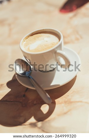 Cup of frothy latte coffee or cappuccino on a wooden table in hot sunshine, close up high angle view with a teaspoon and copyspace - stock photo