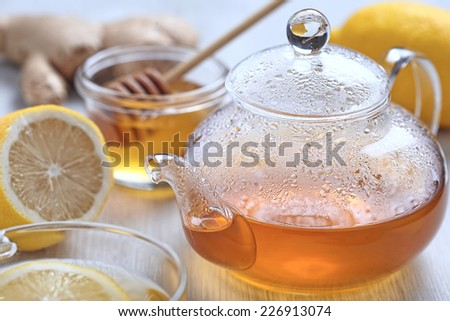 Cup of ginger tea with honey and lemon on wooden table - stock photo