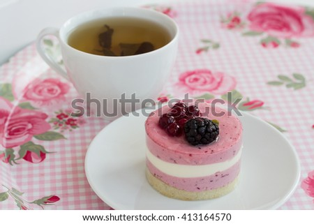 Cup of green tea and biscuit cake with berries on the tray - stock photo