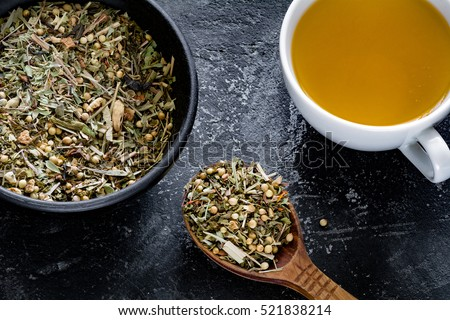 Cup of green tea and dried herbal tea leaves nearby. Healthy, medical product