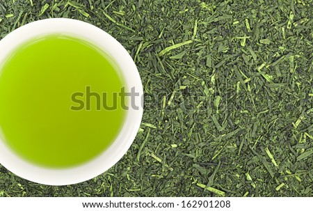 Cup of green tea and green tea leaves background - stock photo