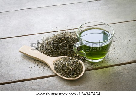 cup of green tea and spoon of dried green tea leaves on wooden background - stock photo