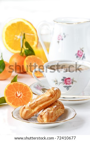 Cup of green tea, eclairs, juice and fruit. Beautiful breakfast.