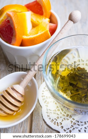 Cup of green tea, fresh fruits and honey