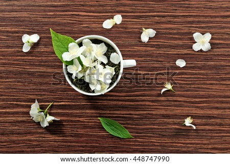 Cup of green tea leaves and jasmine flowers on wooden background