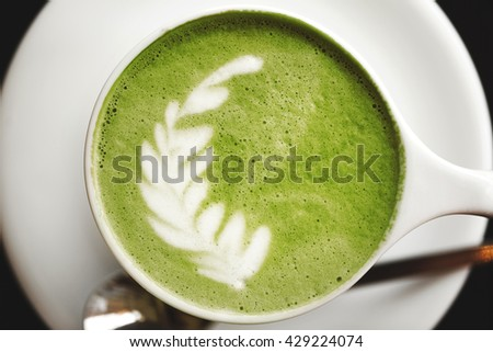 Cup of green tea matcha latte with latte art, standing on wooden table.