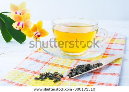 Cup of green tea on orange checkered napkin with a yellow orchid on a white wooden background. Cup tea. Cap of tea. Tea.  Green tea.  Tea time. Cup of green tea. Cup green tea. Dried tea. Tea scoop - stock photo