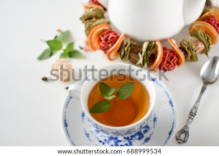 cup of green tea placed on a white table  mint leaves in the cup