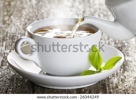 Cup of green tea pouring close up shoot - stock photo