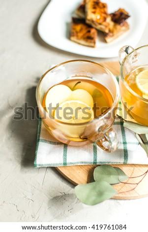 Cup of green tea with cinnamon, lemon and apples, baklava - stock photo