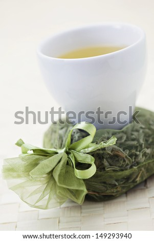 cup of green tea with dry leaves - tea time