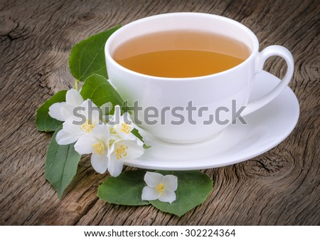 Cup of green tea with jasmine flowers on wooden background - stock photo