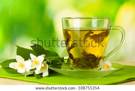 cup of green tea with jasmine flowers on wooden table on green background - stock photo