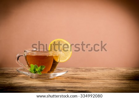 Cup of green tea with mint leaf and lemon slice on old wooden desk, empty space for text - stock photo