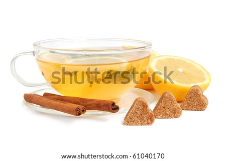 Cup of green tea with mint leaves, lemon, heart-shaped cane sugar and cinnamon sticks on white background - stock photo