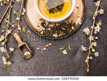 Cup of green tea with sprig of cherry blossoms on dark stone background, top view - stock photo