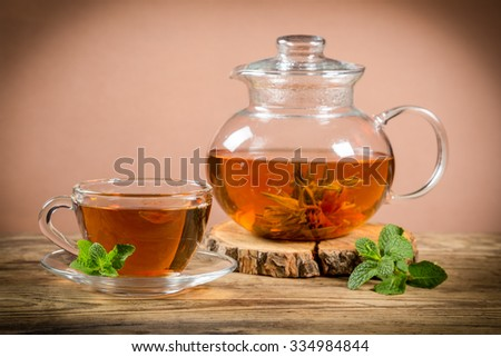 Cup of green tea with teapot on old wooden desk - stock photo