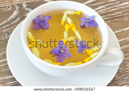 Cup of herb tea with violet and cowslip blossoms on wooden background