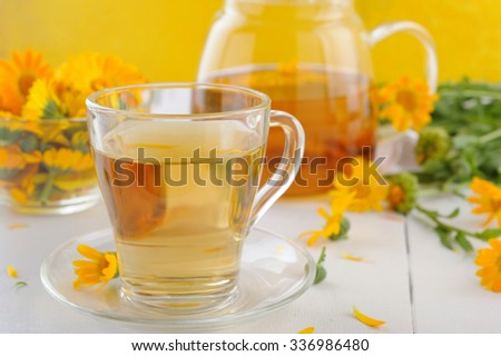 Cup of herbal tea and healing herbs calendula in a glass bowl on yellow background