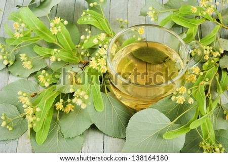 cup of herbal tea and linden blossoms, bright wooden