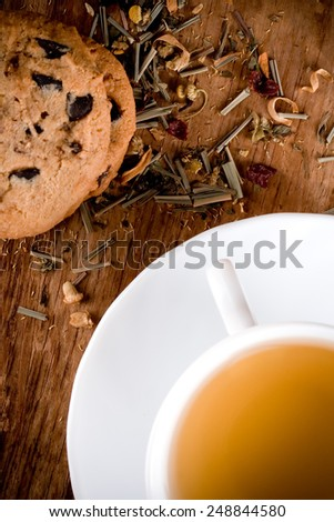 cup of herbal tea and some fresh cookies closeup on wooden table  - stock photo
