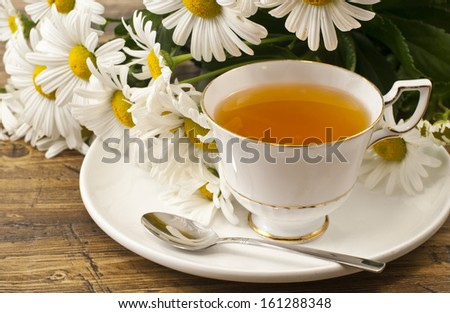 Cup of herbal tea with chamomile flowers - stock photo