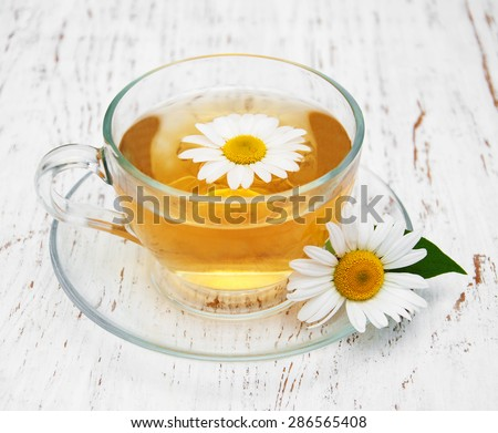Cup of herbal tea with chamomile on a old wooden background - stock photo