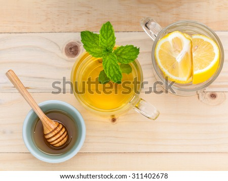 Cup of herbal tea with fresh green mint ,honey and lemon on wooden background.