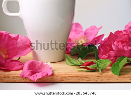 cup of herbal tea with fresh rose hip flowers wooden tray
