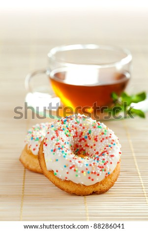 Cup of herbal tea with mint and couple of delicious tasty dough nuts on the beige table mat. - stock photo
