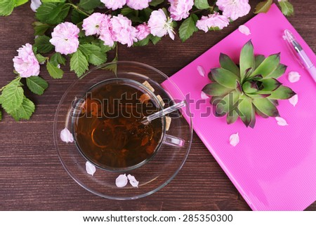 Cup of herbal tea with pink roses on wooden table, top view - stock photo