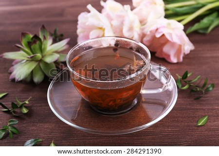 Cup of herbal tea with tulips on wooden table, closeup