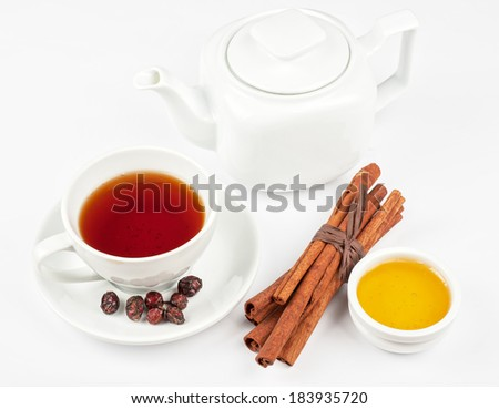 Cup of hot berries tea with cinnamon sticks, and honey - stock photo