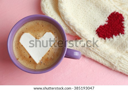 Cup of hot cappuccino with heart marshmallow and warm mittens on pink background, close up