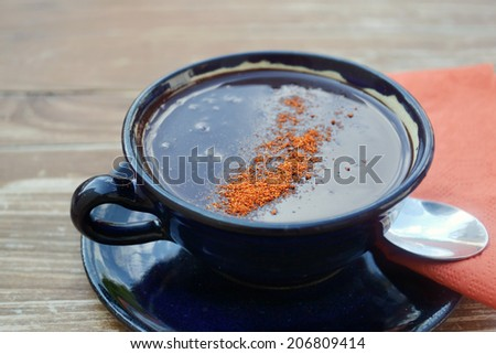 Cup of hot chocolate with chili pepper - stock photo