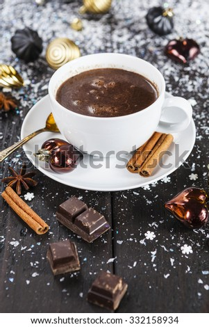 Cup of hot chocolate with christmas ornaments on snowy table - stock photo