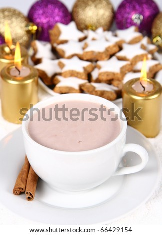 Cup of hot chocolate with cinnamon, star shaped christmas cookies with icing ana gold candles with christmas balls in the background - stock photo
