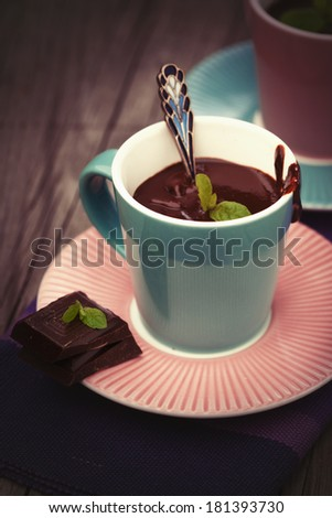 Cup of hot chocolate with mint on old wooden table - stock photo